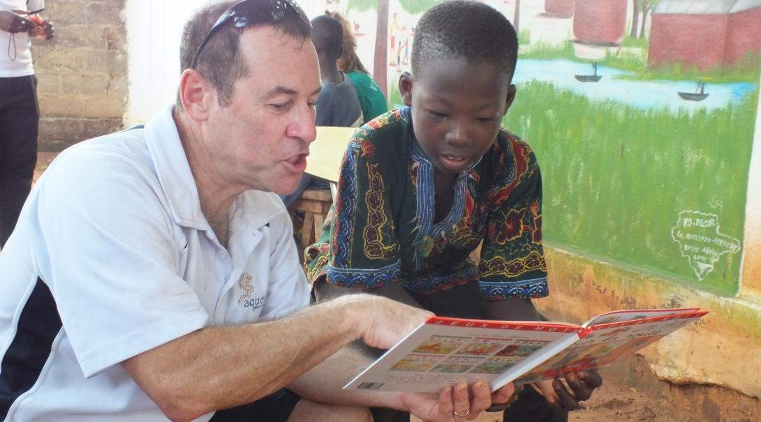 An older man volunteering abroad helps a local child improve his reading at one of our Childcare Projects.